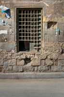 Old abandoned stone bricks wall with one closed grunge broken wooden window covered by wooden grid