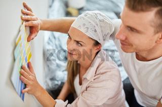 Paar trifft Entscheidung für Wandfarbe bei Renovierung