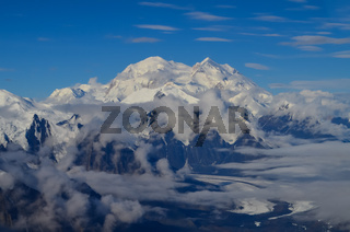 Aerial view of Mount Denali (mt Mckinley) peak from a plane with glaciers around and blue sky above. Denali National Park and Preserve, Alaska, United States