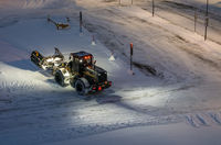 Powerful snowplough clearing parking lot