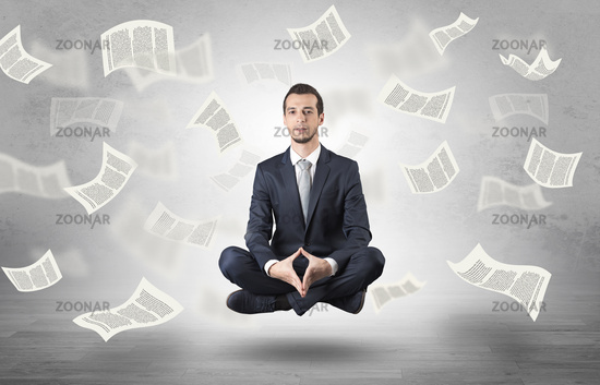 Businessman meditating with flying paper concept