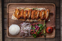 Turkish chicken wings kebab with rice and vegetables on rustic wooden table