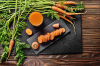Top view at fresh organic vegetarian Carrot juice on wooden kitchen table