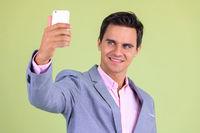 Portrait of happy young handsome businessman taking selfie