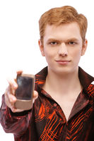 red-haired young man close-up in red shirt shows cell phone isolated on white background