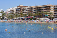 Torrevieja, Spain - June 10, 2019: Waterside view lot of tourists enjoy warm weather summer day on the Playa Del Cura beach, swimming in sea, sunbath on sand in Torrevieja resort, Costa Blanca, Spain