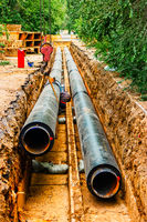 Two New heating water tube pipe in trench covered with black heat isulation