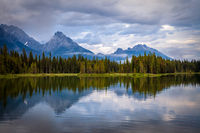 Mountains reflecting in the calm waters of Spillway Lake in Peter Lougheed Provincial Park, Alberta