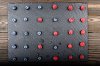 Flat lay view at ripe bilberry and raspberry berries on slate stone tray closeup