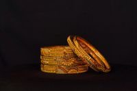 Artificial golden bangles close up on a black background.