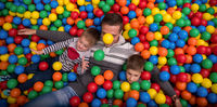 dad and kids playing in pool with colorful balls
