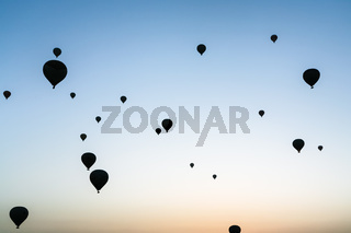 many hot air ballons in sky at sunrise
