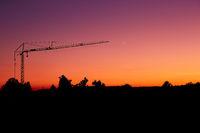 Sonnenuntergang mit Kran und Sichelmond