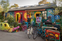 COPENHAGEN, DENMARK - October 2018: Small, colorful art shop in Freetown Christiania, a self-proclaimed autonomous neighbourhood in Copenhagen. Painting of Kim Larsen. Bicycles parked outside.