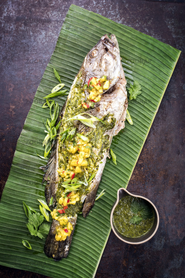 Barbecue white grouper with chimichurri sauce aji criollo and mango chutney as top view in a green banana leaf
