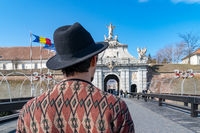 A tourist young man with a hat admiring a fortress gate entrance. A man admiring the 3rd Gate of the Alba-Carolina Fortress in Alba Iulia, Romania. Alba Iulia cityscape