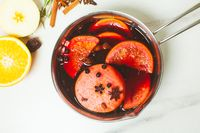 Mulled wine in aluminum casserole on marble background