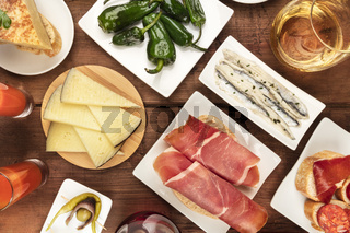 Spanish tapas and wine, the cuisine of Spain shot from the top on a dark rustic wooden background