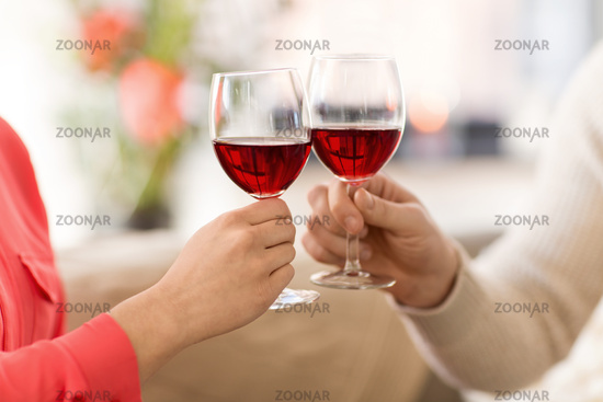 hands of couple clinking red wine glasses