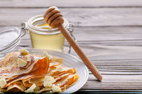 French crepes with butter and honey in ceramic dish on wooden kitchen table
