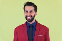 Face of young happy bearded Persian businessman in suit thinking