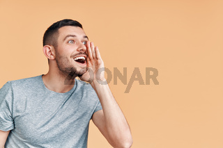 Young handsome man shouting and screaming loud to side with hand on mouth and copy space for text