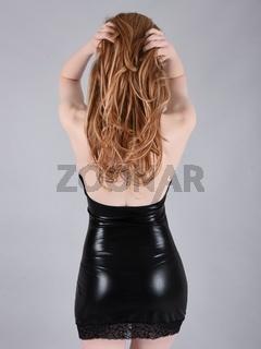 Ashley Foxx, sexy, vollbusige Rothaarige gekleidet in einem glanzenden schwarzen PVC-Kleid
