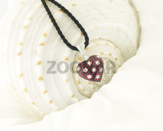 White Gold Heart Pendant With Rubies And Diamonds On SeaShell Background