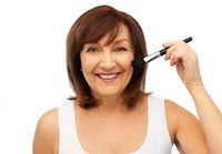 smiling senior woman with make up blush brush