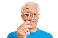 Alter Mann schaut mit Auge durch Lupe