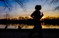 Silhouette of man and woman run together on a sunset on lake coast.