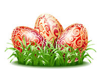 Easter background with three red eggs in grass