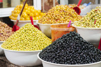 Market stall with marinated green and black olives.