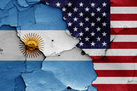 flags of Argentina and USA painted on cracked wall