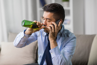 man drinking alcohol and calling on smartphone