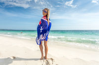 Smiling woman with Australian flag wrapped around her body sunny