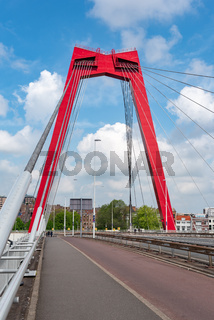 Red cable bridge against blue sky and white clouds