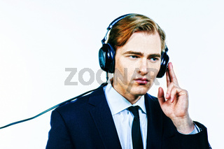 Man in suit listening to music on headphones