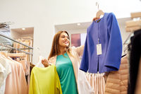 happy woman choosing clothes at clothing store