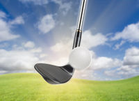 Black Golf Club Wedge Iron Hitting Golf Ball Against Grass and Blue Sky Background