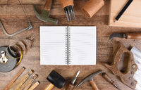 High angle closeup of a large group of tools arranged around an open note book with blank pages.