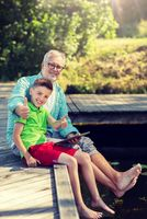 grandfather and boy with tablet pc on river berth