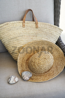 Closeup of straw hat and purse in chair