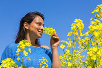 Woman smelling yellow flower in rapeseed field