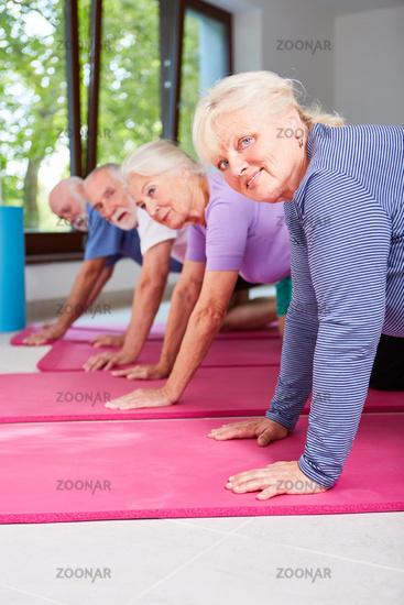 Senioren beim Rehasport machen Liegestütz