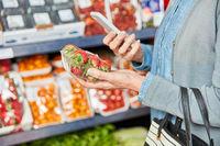 Kundin scannt Packung Erdbeeren mit Smartphone