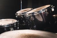 Closeup view of a drum set in a dark studio. Black drum barrels with chrome trim. The concept of live performances