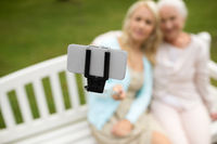 daughter and senior mother taking selfie at park