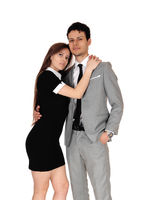 A lovely young couple standing and she is hugging him