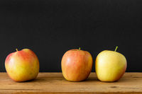 black background three apples wooden table